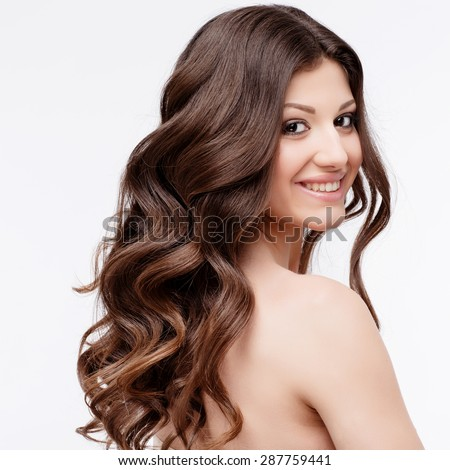 Beautiful Woman with curly brown hair close up. Youth Skin anf Hair Care Concept - stock photo