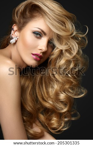 Beautiful woman with curly hair on a gray background