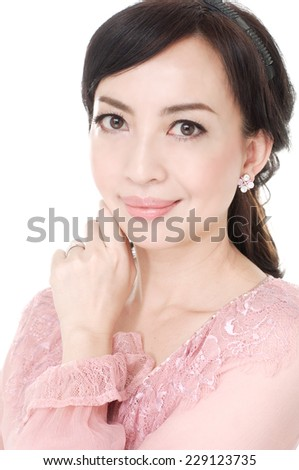 Beautiful woman with curly hairs poses at studio - stock photo
