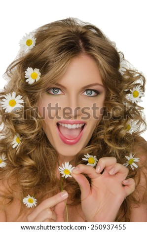 beautiful woman with daisies in curly hair takes petals - stock photo