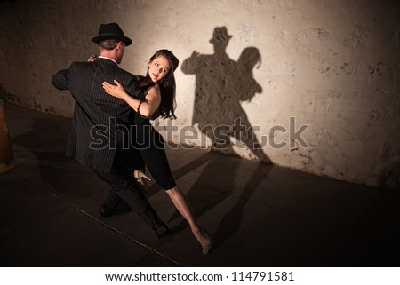Beautiful woman with dance partner performing a tango routine - stock photo