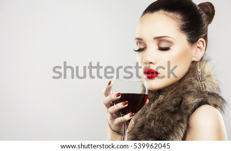 beautiful woman with dark makeup and red lipstick posing on light grey background. Drinking glass of red wine.