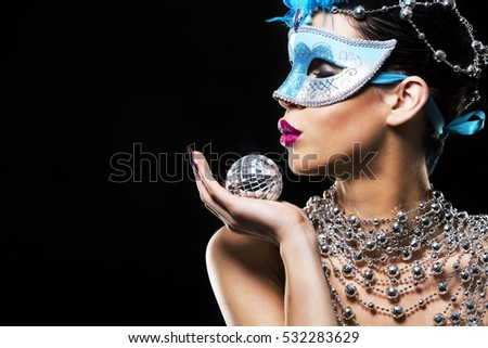 beautiful woman with dark makeup wearing blue and silver mask surrounded by party accessories on light black background