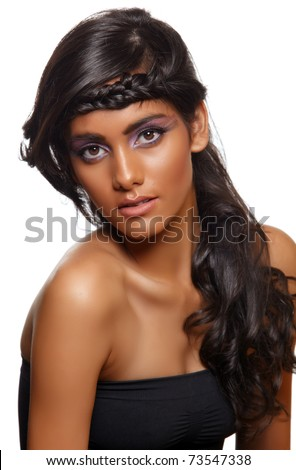 beautiful woman with dark tanned skin and long curly black hair with braid wearing purple artistic make-up with long eyelashes. - stock photo