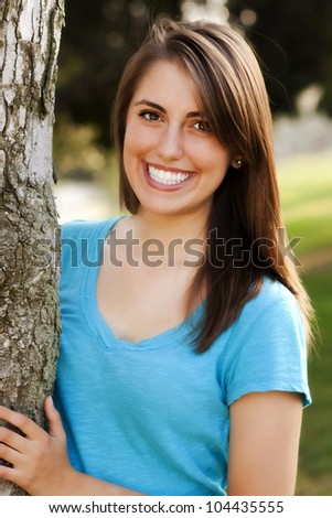 beautiful woman with dazzling smile peeks out from behind a tree - stock photo