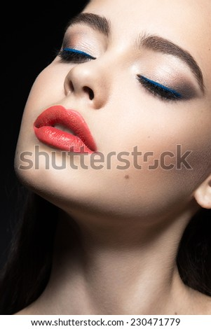 Beautiful woman with evening make-up and red lips. Beauty face. Picture taken in the studio on a black background. - stock photo