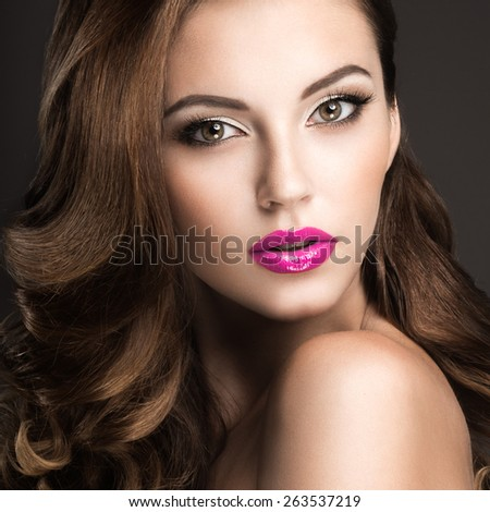 Beautiful woman with evening make-up, pink lips and curls. Beauty face. Picture taken in the studio on a gray background. - stock photo