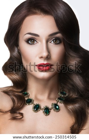 Beautiful woman with evening make-up, red lips and curls. Beauty face. Picture taken in the studio on a white background.