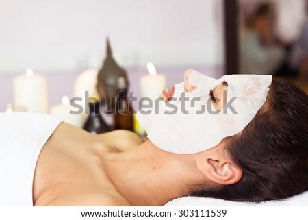 Beautiful woman with facial mask at beauty salon. Spa treatment - stock photo