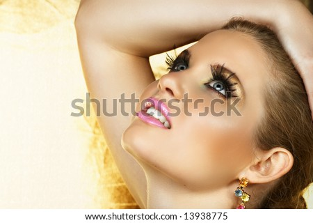 beautiful woman with fantasy golden eye make-up and good skin texture and pore definition - stock photo