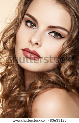 Beautiful woman with fashion make-up and shiny curly hair. Elegant hairstyle for long hair - stock photo