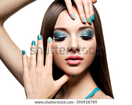 Beautiful woman with fashion makeup and green nails. Pretty young adult girl with straight brown hair - stock photo