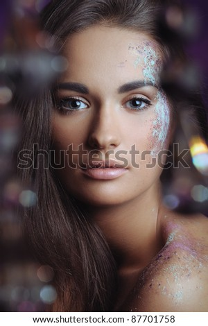 beautiful woman with festive makeup in color spray and boke lights - stock photo