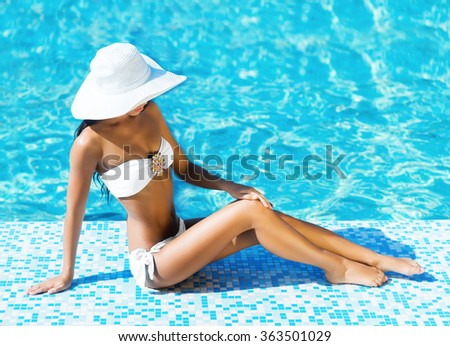 Beautiful woman with fit, tanned body in hat and alluring bikini sitting and tanning poolside. - stock photo