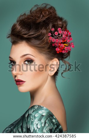Beautiful woman with flower on her head. Beauty girl with flowers hairstyle. Perfect makeup. Beauty fashion.