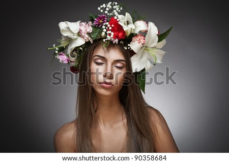 Beautiful woman with flower wreath on black background - stock photo