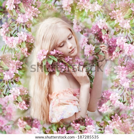 Beautiful woman with flowering tree. Beauty young girl in garden. - stock photo