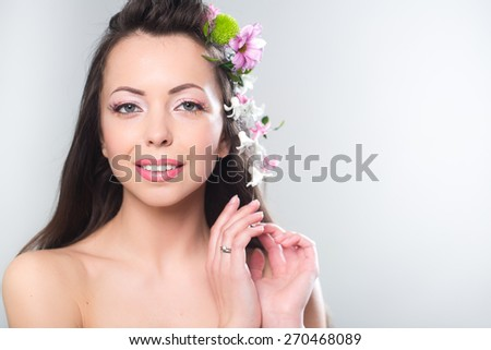 Beautiful woman with flowers in hair. Space for text. - stock photo