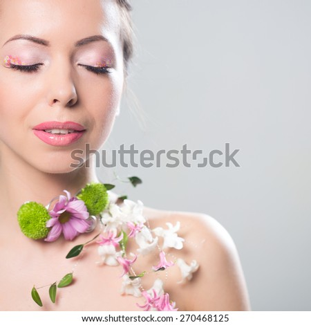 Beautiful woman with flowers on the showlder. Space for text. - stock photo
