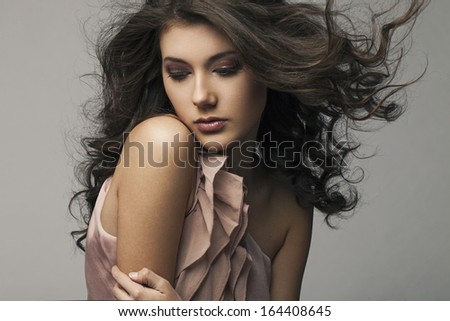 Beautiful woman with flying hair and evening make-up.