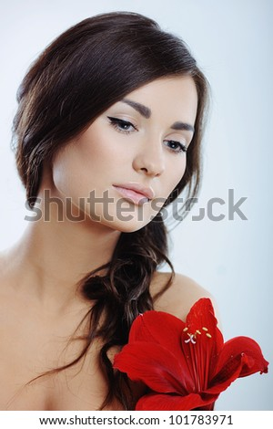 Beautiful woman with fresh health skin of face and red flower in hand - stock photo
