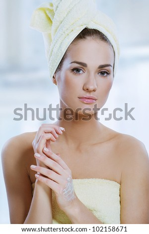 beautiful woman with fresh healthy skin applying hand cream after bath. Spa woman concept - stock photo