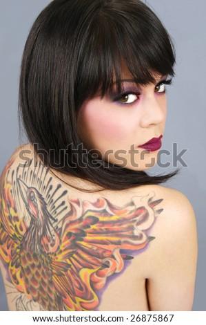 Beautiful woman with full back tattoo - stock photo