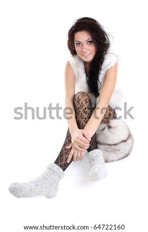 beautiful woman with fur hat  sitting over white background