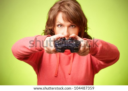 Beautiful woman with gamepad playing videogame over green background. Focus on gamepad - stock photo