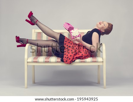 Beautiful woman with gift box in hands laughing while sitting on a sofa in a retro style. - stock photo