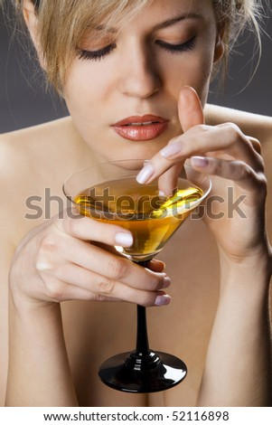 Beautiful woman with glass of cocktail going wool-gathering - stock photo