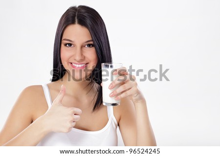 Beautiful woman with glass of milk and thumb up - stock photo