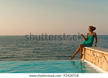 Beautiful woman with glass of wine sitting on the edge of infinity pool like greek style. Crete. Greece - stock photo