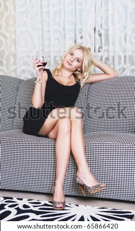 Beautiful woman with goblet of wine sitting on sofa