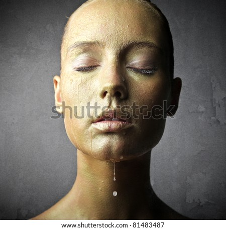 Beautiful woman with golden foundation - stock photo
