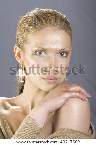 Beautiful woman with golden make up - Close up portrait of a beautiful female model - stock photo