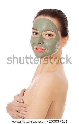 Beautiful woman with green clay facial mask - stock photo