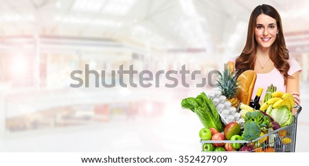 Beautiful woman with grocery shopping cart over shop background.