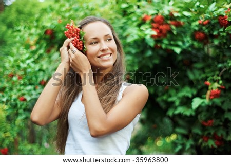 Beautiful woman with guelder rose in hair - stock photo