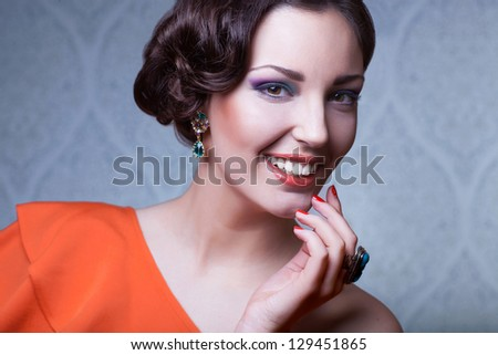 beautiful  woman with hairstyle posing in studio with jewerly, close up portrait - stock photo