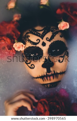 Beautiful woman with halloween sugar skull make-up and flowers in her hair. Girl lying in water and looking at the camera. Makeup girl like sugar skull - a symbol of Day of the Dead holiday. - stock photo