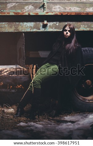 Beautiful woman with halloween sugar skull make-up with old truck on background at night. Makeup girl like sugar skull - a symbol of Day of the Dead holiday. Symbolism to celebrate Day of the Dead. - stock photo