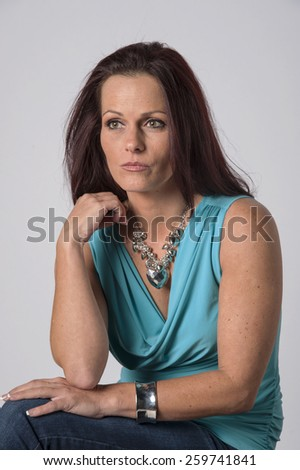 Beautiful woman with hand on a sofa - stock photo