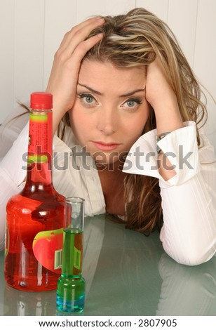Beautiful woman with hands in hair and bottle and glass within reach