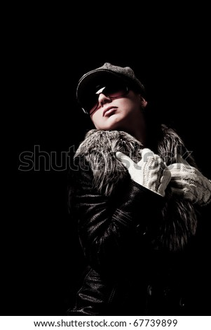 beautiful woman with hat and sunglasses wearing a coat on black background