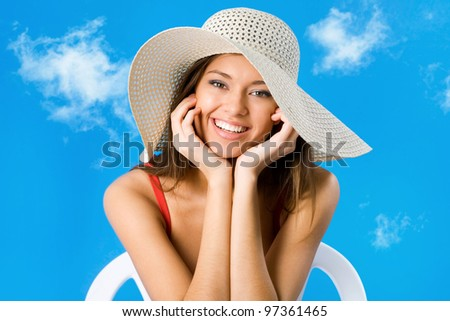 Beautiful woman with hat smiling on a background of blue sky