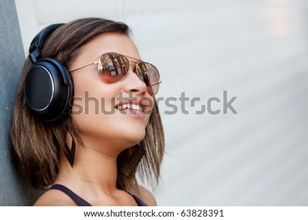 Beautiful woman with headphones and wearing sunglasses