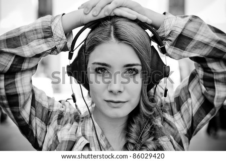 Beautiful woman with headphones on city - stock photo