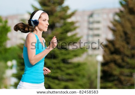Beautiful woman with headphones running in green park on sunny summer day - stock photo
