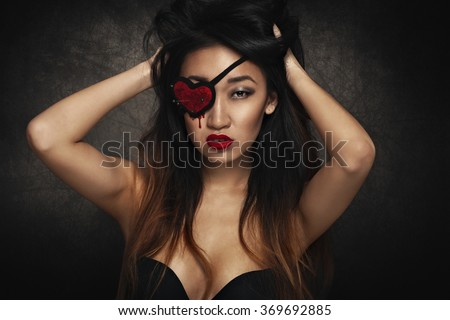 Beautiful woman with heart shape eye patch - stock photo
